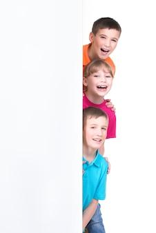 Grupo alegre de crianças atrás de uma bandeira branca - isolada no fundo branco.
