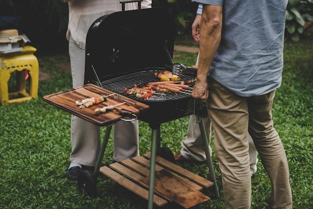 Grupo, amigos, de, sênior, cozinhar churrasco, ligado, a, churrasqueira, em, partido, casa, jardim