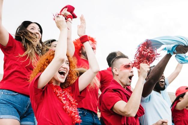 Grupo animado de amigos multirraciais assistindo a um jogo de futebol