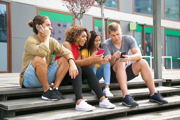 Grupo animado de amigos usando telefone celular
