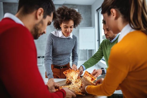 Grupo animado de empresários almoçando pizza