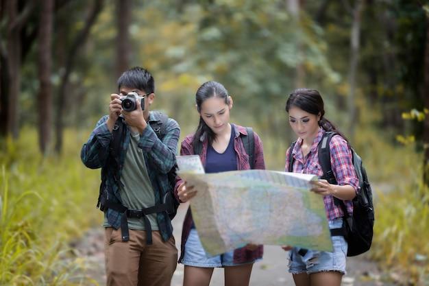 Grupo asiático caminhadas com mochilas de amigos caminhando juntos e olhando o mapa