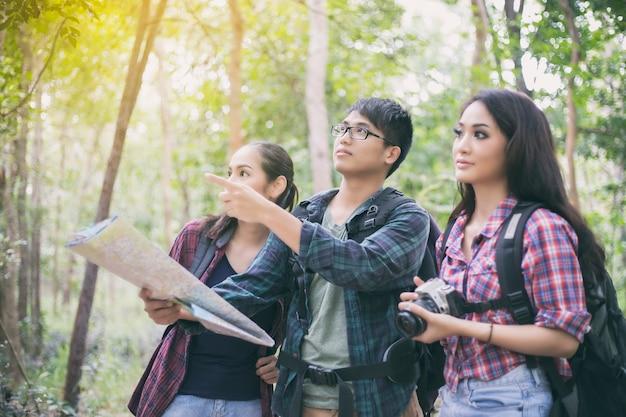 Grupo asiático com amigo caminhando juntos procurando mapa