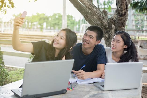 Grupo asiático de estudantes sorrindo e selfie com o amigo