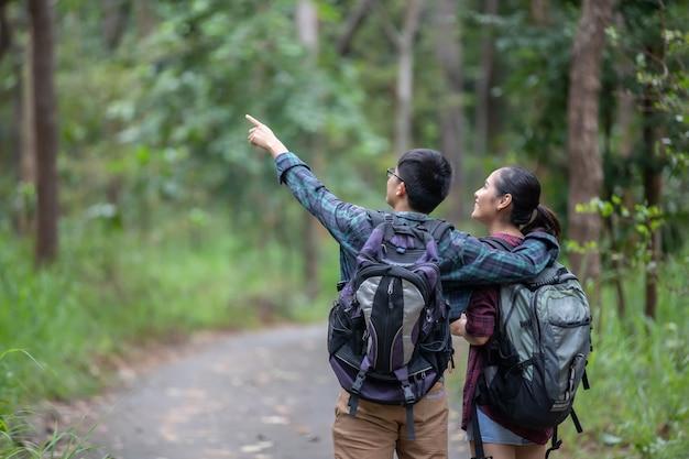 Grupo asiático de jovens caminhadas com mochilas de amigos caminhando juntos e olhando o mapa e takin