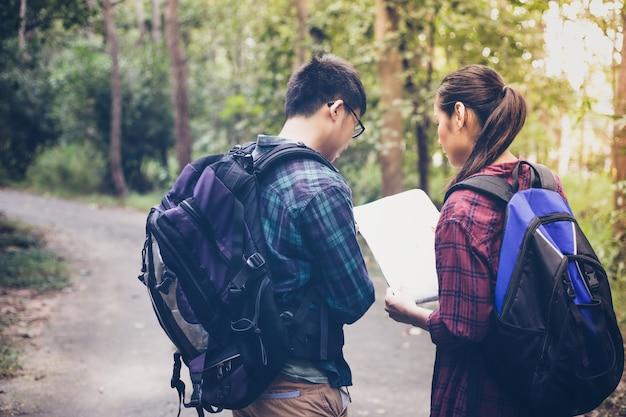 Grupo asiático de jovens caminhando com mochilas de amigos caminhando juntos
