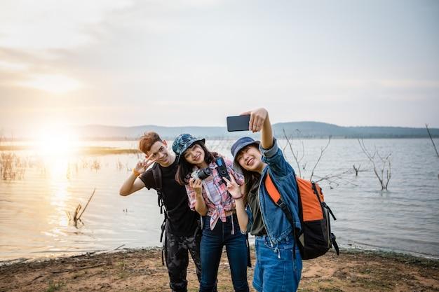 Grupo asiático de jovens com amigos e mochilas caminhando juntos e amigos felizes estão tirando foto e selfie, relaxe o tempo nas viagens de férias