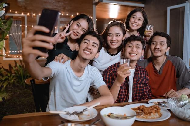 Grupo asiático de melhor amiga tira selfie com smartphone enquanto faz festa no jardim