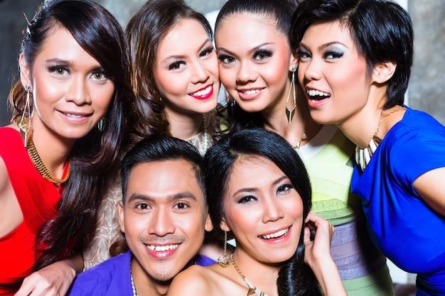Grupo asiático jovem e bonito de pessoas festeiras ou amigos tirando fotos em uma boate chique