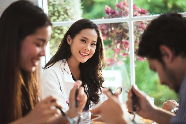 Grupo asiático que come o restaurante, ela sorria.