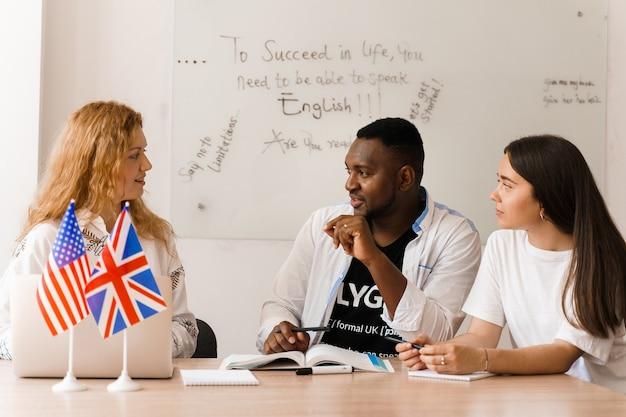 Grupo atraente multiétnico on-line de professores estudam e riem, discutem algo