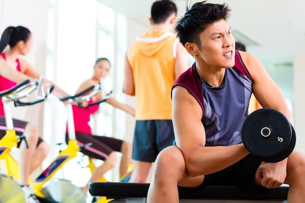 Grupo chinês asiático de homens e mulheres fazendo exercícios esportivos ou treinando em uma academia de ginástica com barra e pesos para obter mais potência