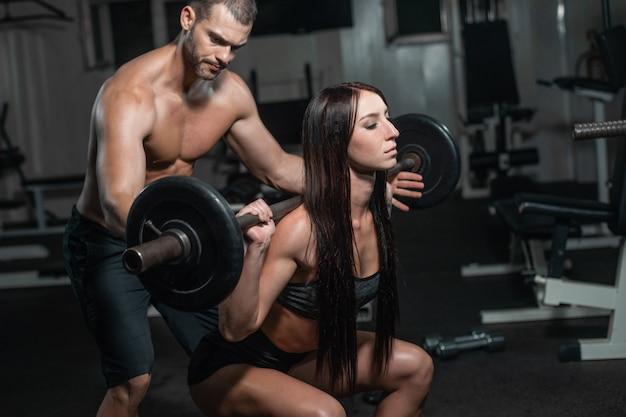 Grupo com equipamento de treinamento de peso de haltere no ginásio de esporte