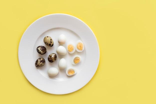 Grupo, conjunto de pequenos ovos de codorna orgânicos descascados e com casca, cortados ao meio, cozidos ao meio e crus em um prato branco vista superior de cima. antes de cozinhar e depois. gema de ovo