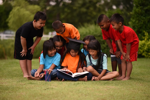 Grupo crianças, leitura mentindo, ligado, campo grama