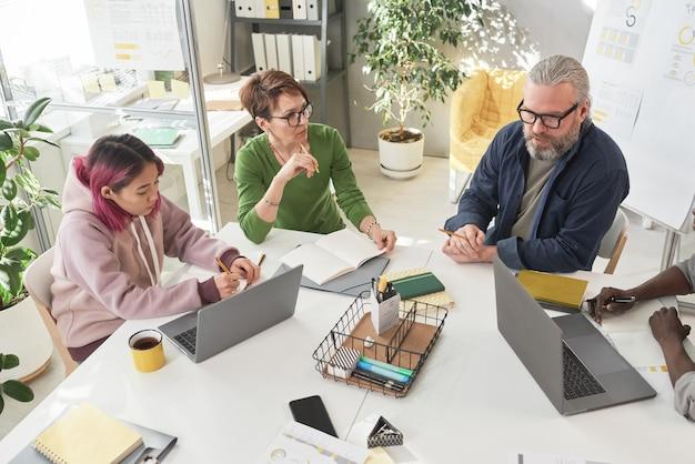 Grupo da equipe de negócios sentado à mesa e discutindo momentos de trabalho durante a reunião de negócios no escritório