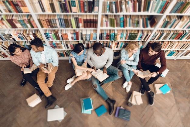 Grupo da vista superior de estudantes multiculturais étnicos na biblioteca.