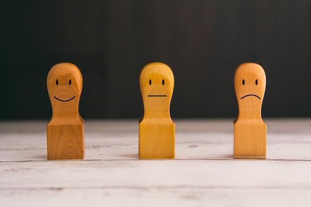 Grupo de 3 modelos de madeira que expressam expressões faciais