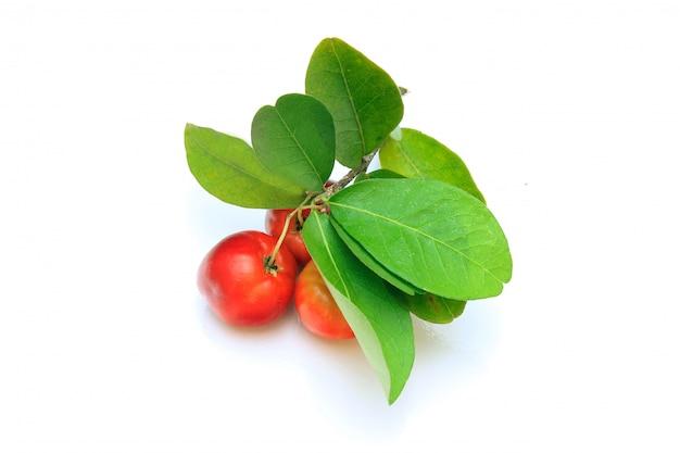 Grupo de acerola orgânica fresca com folhas verdes, isolado no fundo branco