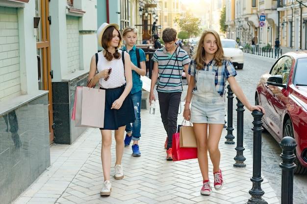 Grupo de adolescentes com sacos de compras na rua da cidade.