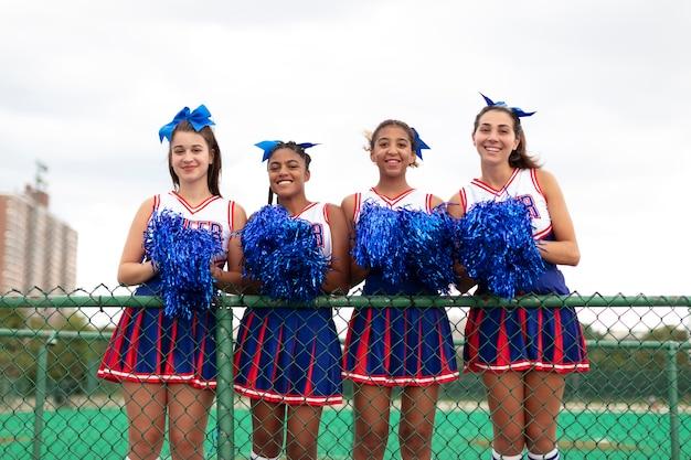 Grupo de adolescentes com uniforme fofo de líder de torcida