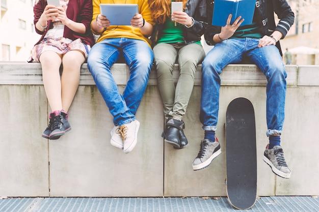 Grupo de adolescentes fazendo atividades diferentes, sentado em uma área urbana