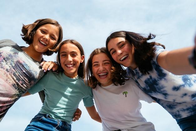 Grupo de adolescentes felizes e sorridentes, passando o lazer ao ar livre