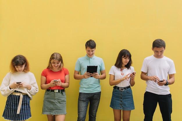 Grupo de adolescentes que usam seus telefones celulares e tabuleta em um fundo amarelo.