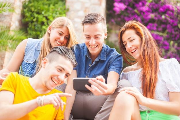 Grupo de adolescentes rindo e olhando para um telefone inteligente