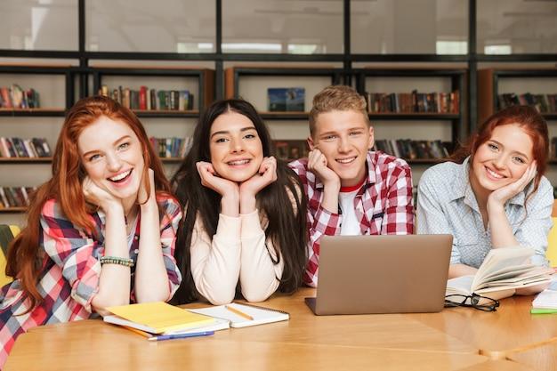 Grupo de adolescentes sorridentes fazendo lição de casa