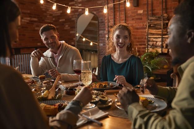 Grupo de adultos alegres sentados à mesa de jantar enquanto aproveitam a festa com iluminação externa