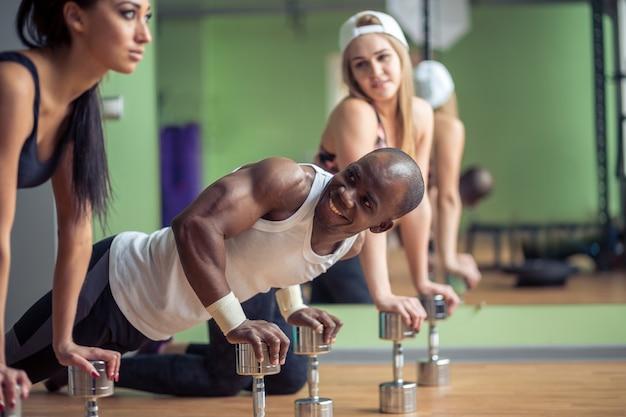 Grupo de adultos realizando exercícios de flexão na instalação de exercícios de cross-fitness de aptidão física interior com reflexo de luz brilhante sobre eles
