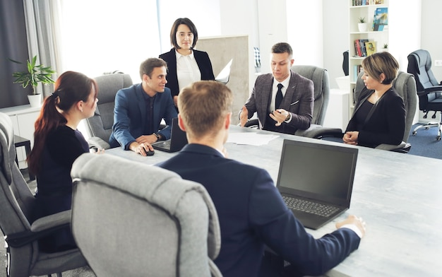 Grupo de advogados de jovens empresários de sucesso se comunicando em uma sala de conferências enquanto trabalham em um projeto