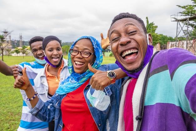 Grupo de alegres amigos africanos com máscaras tirando uma selfie em um parque