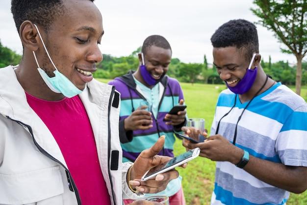 Grupo de alegres amigos africanos com máscaras tomando uma bebida e usando seus telefones em um parque