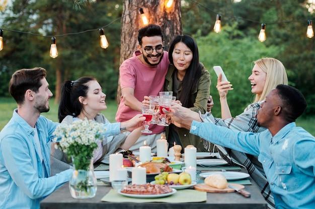 Grupo de alegres amigos interculturais reunidos à mesa servidos sob uma árvore tilintando de taças com vinho caseiro