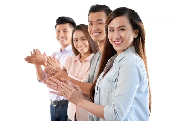 Grupo de alegres asiáticos em pé na fila e batendo palmas de mãos