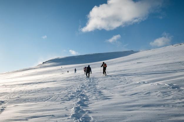 Grupo de alpinistas escalando colina nevada e céu azul no inverno nas ilhas lofoten, noruega