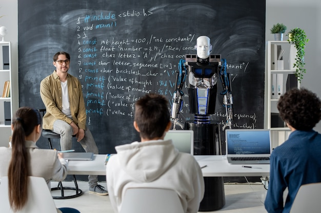 Grupo de alunos adolescentes olhando para o robô parado no quadro-negro e descrevendo suas características técnicas para o professor no seminário