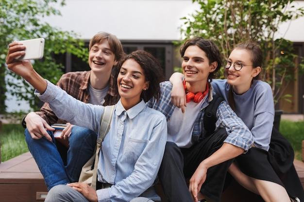 Grupo de alunos alegres sentados e tirando fotos bonitas no celular enquanto passam um tempo juntos no pátio da universidade