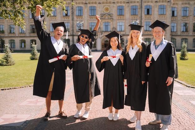 Grupo de alunos alegres usando vestidos de formatura e bonés de mestre