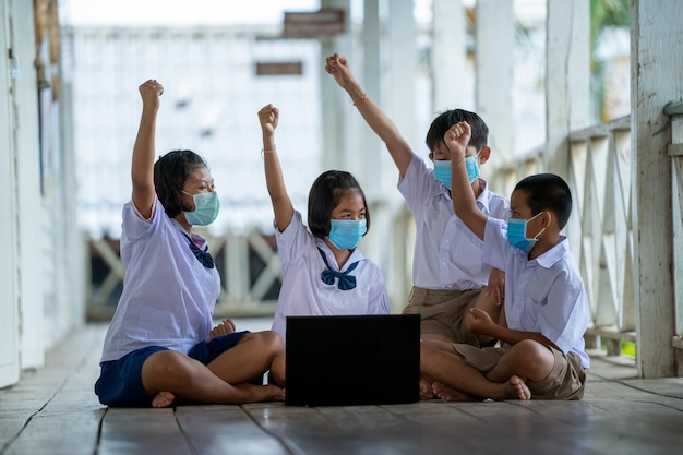 Grupo de alunos asiáticos do ensino fundamental usando máscara higiênica para prevenir o surto de covid 19 enquanto voltavam às aulas reabrir sua escola.