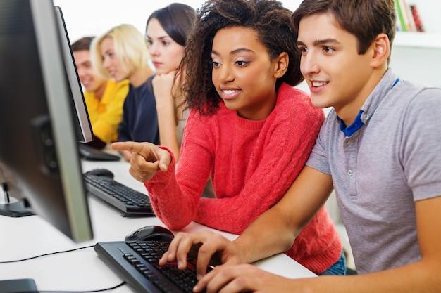 Grupo de alunos com computador na aula em sala de aula