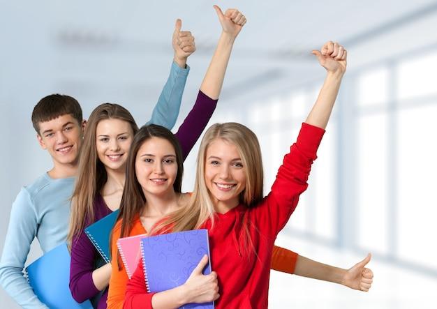 Grupo de alunos com livros isolados sobre um fundo branco