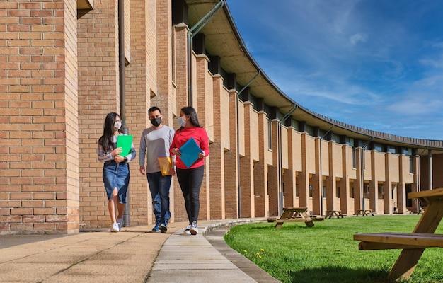 Grupo de alunos com máscara protetora caminhando em um campus universitário