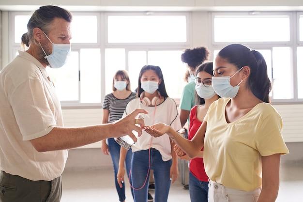 Grupo de alunos com máscaras esperam na fila para entrar na sala de aula e o professor aplica hidroálcool