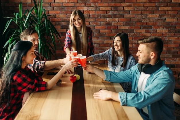 Grupo de alunos comemora evento. jovens com bebidas à mesa no café da faculdade