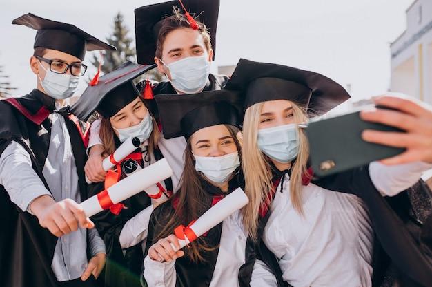 Grupo de alunos comemorando a formatura juntos e usando máscaras