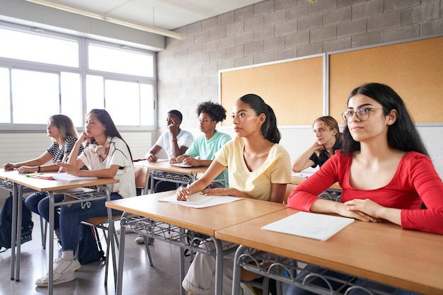 Grupo de alunos de diferentes etnias sentado em sala de aula atendendo o professor jovens