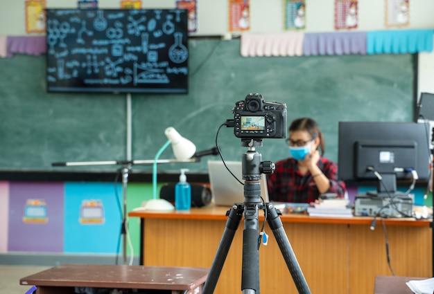 Grupo de alunos do ensino fundamental com o professor sentado na sala de aula online